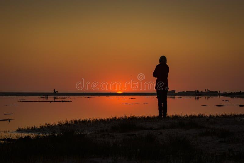 Le soleil plonge au-dessous de l'horizon en tant que montres d'un spectateur image libre de droits