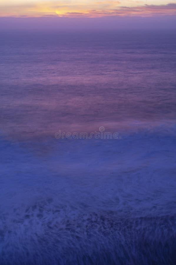 Le soleil plonge au-dessous de l'horizon, peignant une palette des roses et des bleus au-dessus de l'océan pacifique images stock