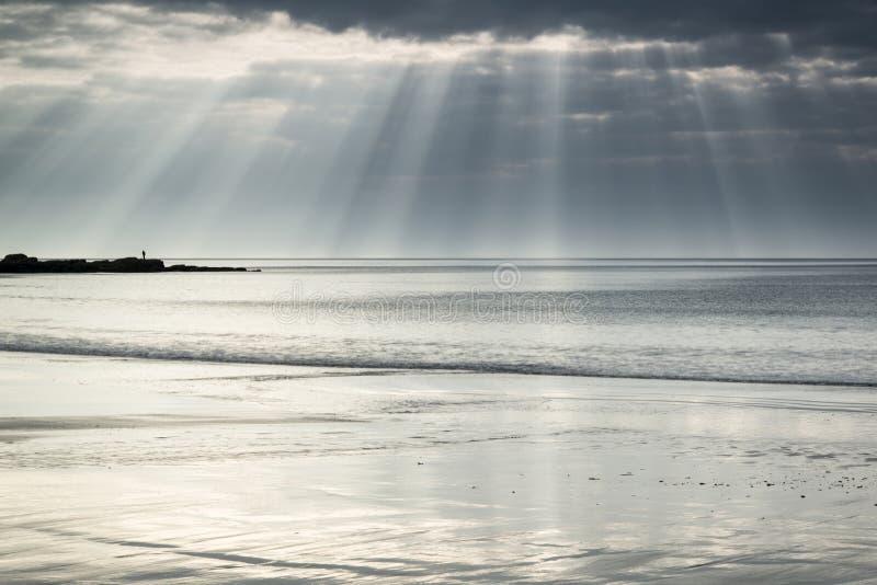 Le soleil renversant rayonne l'éclatement du ciel au-dessus de la plage à sable jaune vide photographie stock