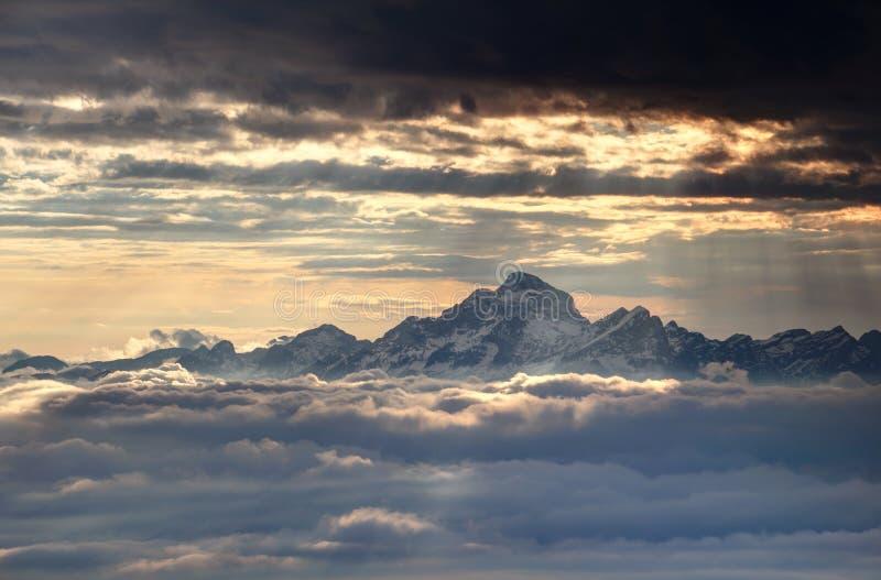 Le soleil rougeoyant rayonne au-dessus de Julian Alps et de la mer neigeux des nuages photos libres de droits