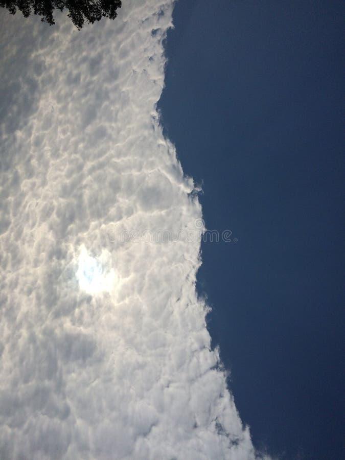 Le soleil se cachant dans les nuages photographie stock libre de droits