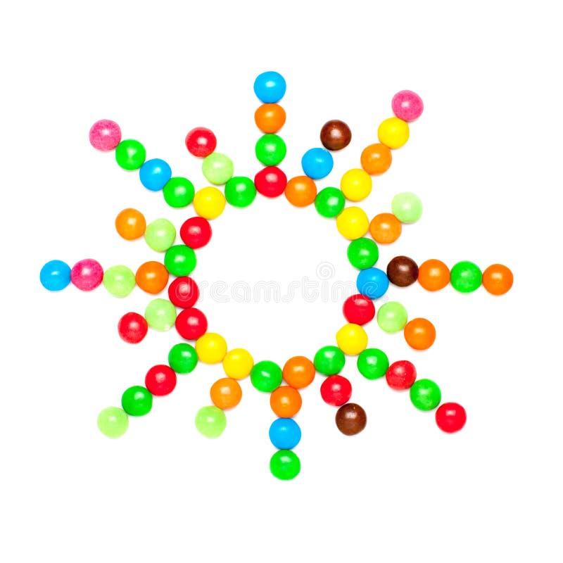 Le SOLEIL se compose des bonbons au chocolat colorés doux d'isolement sur le fond blanc photos libres de droits