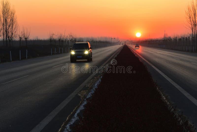 Le soleil se lève à l'extrémité du tronçon de la route images libres de droits