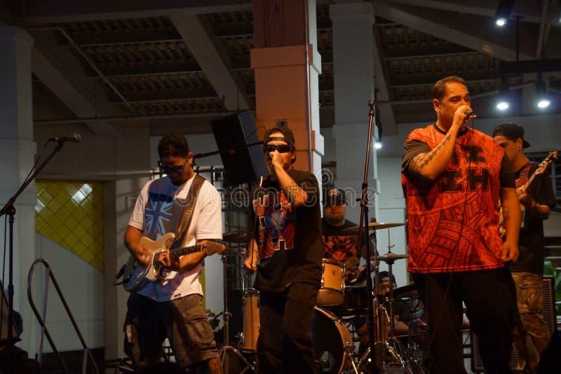 Le soliste di Peni Dean che cantano nel mic come banda si inceppa in scena fotografia stock