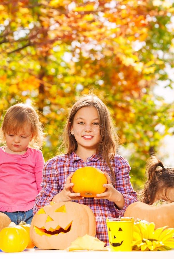 Le sorelle scavano le zucche di Halloween nel giardino immagini stock