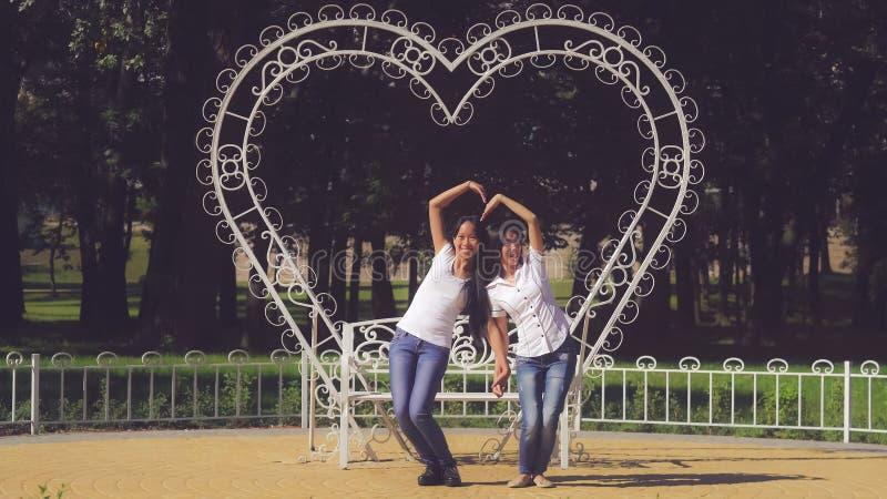 Le sorelle si divertono mostrando l'amore del segnale fotografie stock libere da diritti
