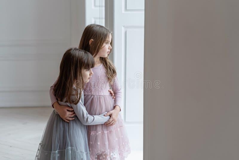 Le sorelline serie in bei vestiti stanno vicino ad una finestra immagini stock libere da diritti