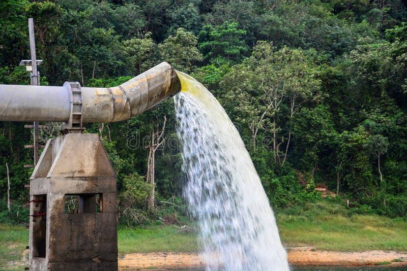 Le sort de l'eau jaillissant hors du grand tuyau en m?tal au lac, l'eau de pompe compl?tent le r?servoir image libre de droits