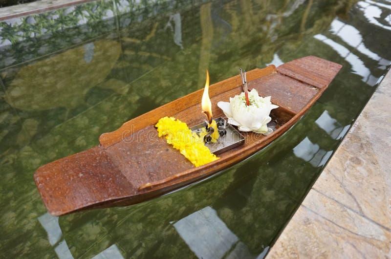 Le souci et le lotus blanc avec la bougie dans le mini bateau en bois sur l'eau claire, utilisation de personnes thaïlandaises po image stock
