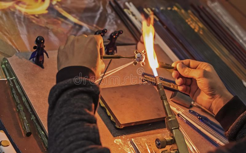 Le souffleur de verre fait une figurine du verre Verre de fonte sur un brûleur à gaz photographie stock libre de droits