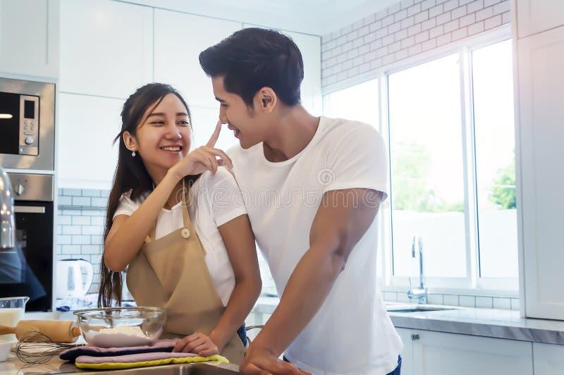 Le sourire affectueux de beaux jeunes couples asiatiques regarde ? la cuisson dans la cuisine ? la maison photos stock