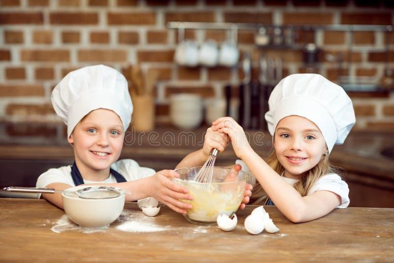 Le sourire badine dans des chapeaux de chef faisant la pâte pour des biscuits photographie stock libre de droits