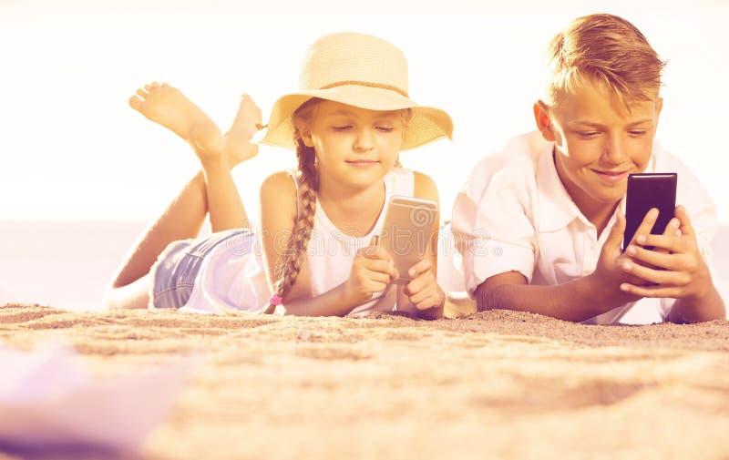 Le sourire badine sur la plage avec le téléphone dans des mains image stock