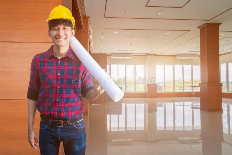 Le sourire d'ingénieur dedans décorent la pièce intérieure accomplie la main tenant les modèles roulés et portent le casque jaune photos libres de droits