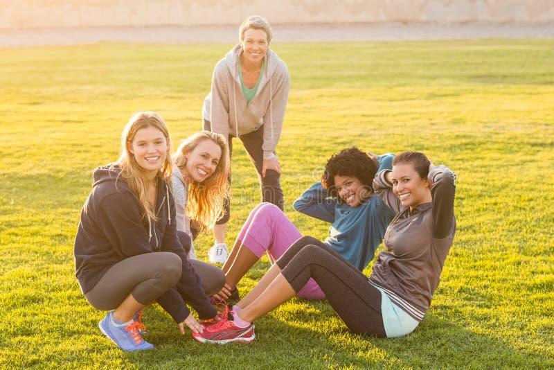 Le sourire des femmes sportives que faire se reposent se lève pendant la classe de forme physique images stock