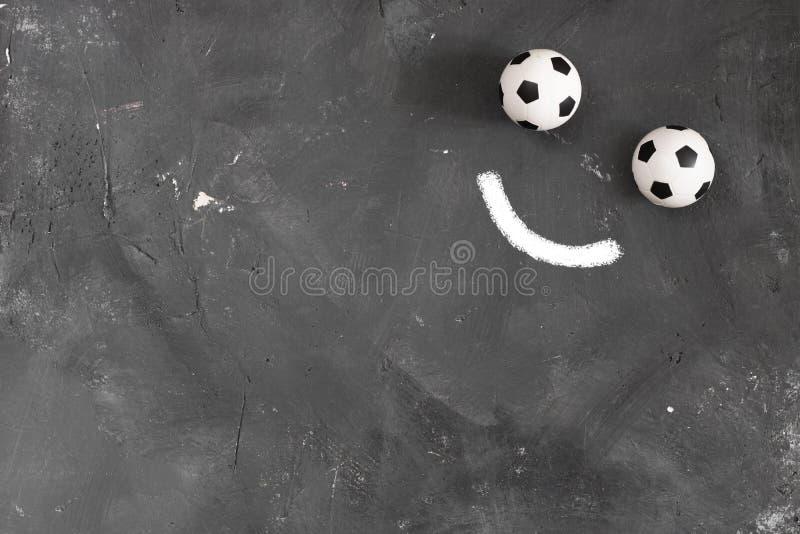 Le sourire a fait de deux petites boules du football et marque la ligne à la craie sur le fond texturisé foncé de tableau noir av photos libres de droits