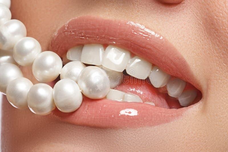Le sourire femelle heureux en gros plan avec les dents blanches saines, les lèvres rouges lumineuses préparent Soin de cosmétolog photos stock