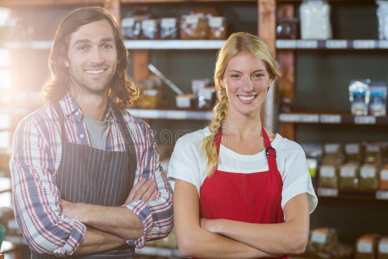 Le sourire fournit la position de personnel avec des bras croisés dans le supermarché photo stock