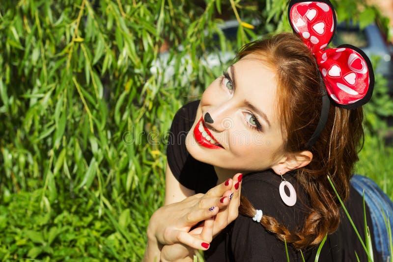 Le sourire heureux de belle fille dans le costume d'une souris avec un grand rouge cintrent vers le bas sur l'herbe en parc photographie stock libre de droits