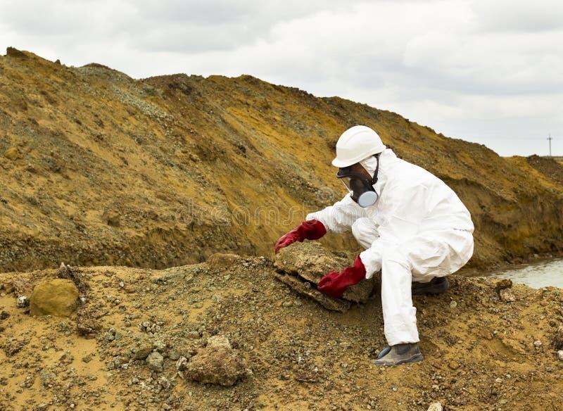 Le spécialiste dans les vêtements de protection prélève un échantillon du sol dedans photo stock