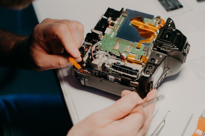 Le spécialiste travaille au centre de service, utilise les outils professionnels Équipement photographique sur la table blanche C photo stock