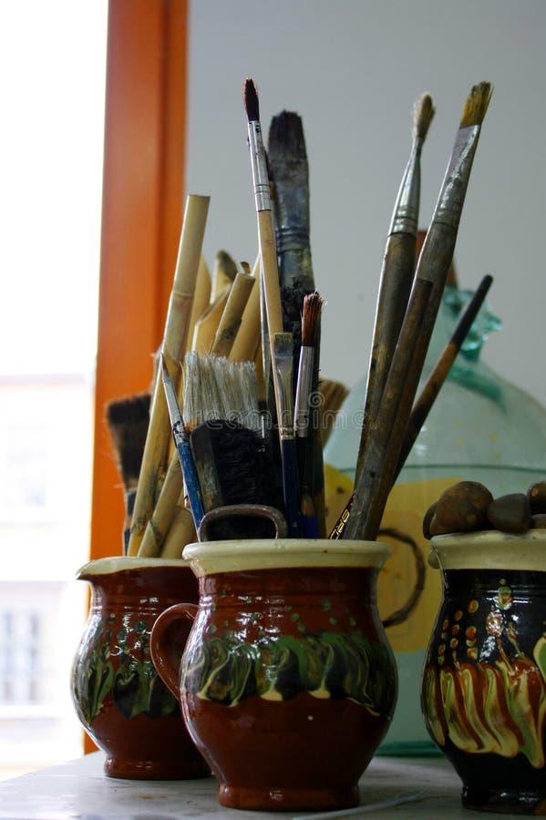 Le spazzole di pittura usate in ceramica hanno dipinto i vasi fotografia stock