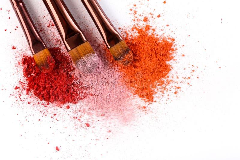 Le spazzole di trucco con arrossiscono o ombretto dei toni rosa, rossi e di corallo spruzzato su fondo bianco fotografia stock libera da diritti