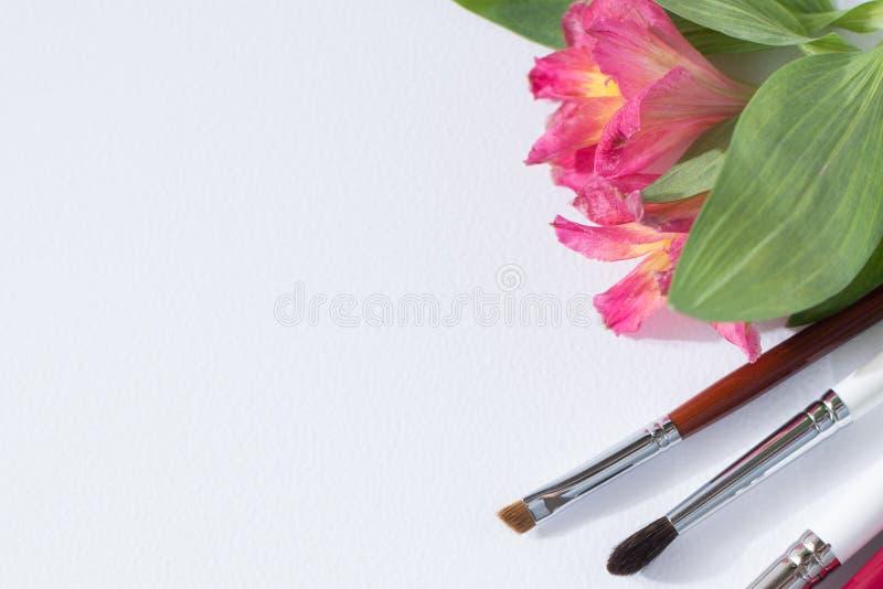 Le spazzole professionali degli strumenti di trucco, gli ombretti, i lipgloss, fiori pongono pianamente lo spazio della copia del fotografia stock