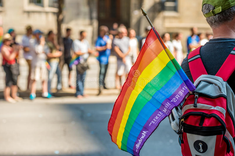 Le spectateur masculin porte le drapeau gai d'arc-en-ciel pendant la fierté de Montréal photographie stock