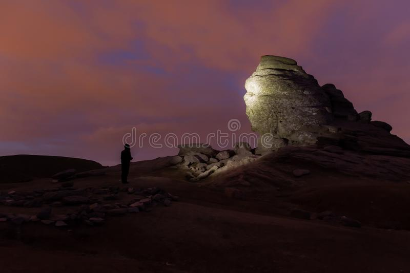 Le sphinx en parc naturel de Bucegi la nuit, illuminé par la lampe-torche photo stock
