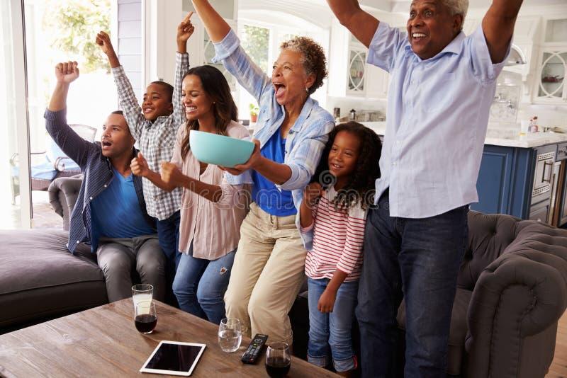 Le sport de observation de génération de famille multi de noir à la TV célèbrent images libres de droits