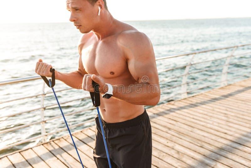 Le sportif dehors sur la plage font des exercices avec l'équipement de sport photographie stock libre de droits