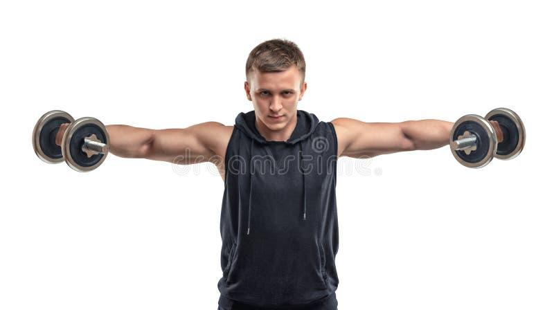 Le sportif sûr de Coutout soulève des haltères pour former ses épaules et deltoïdes images stock
