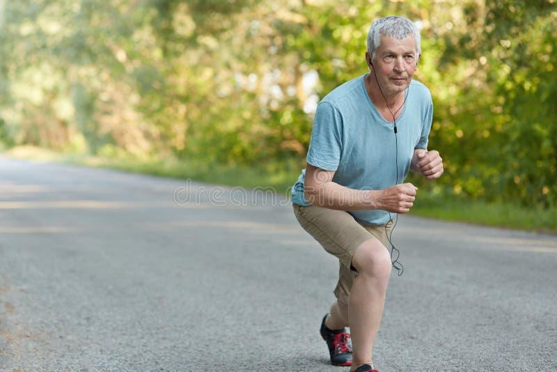 Le sportif supérieur assuré prêt à commencer à pulser le marathon, écoute musique pour s'amuser pendant la formation, habillée in images stock
