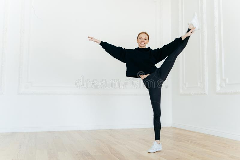 Le sportiga kvinnliga ställningar på ett ben i konditionmitt, visar trevlig fysisk elasticitet, har slank kroppform som är iklädd royaltyfri bild