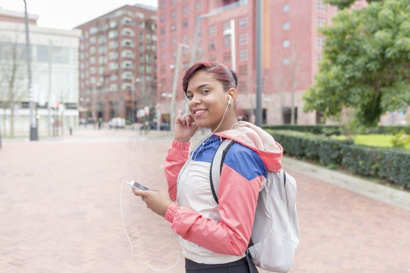 Le sportkvinnan med hörlurar och ila telefonen royaltyfri foto