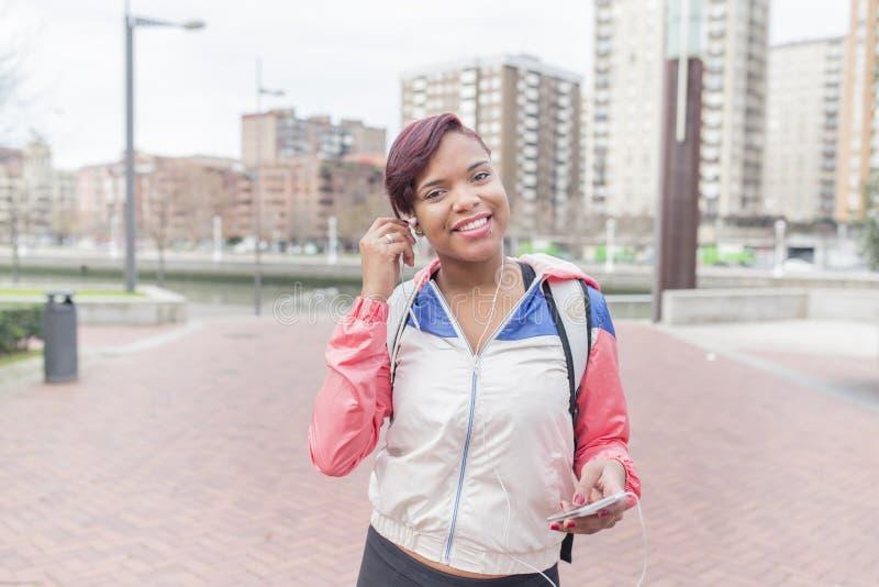 Le sportkvinnan med hörlurar och ila telefonen arkivbild