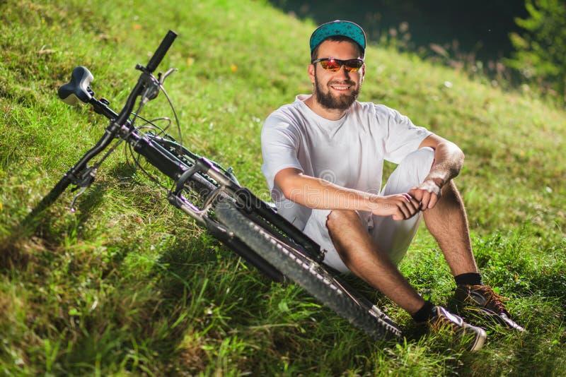 Le sportpojken sitt på gräset nära den utomhus- cykeln royaltyfri fotografi
