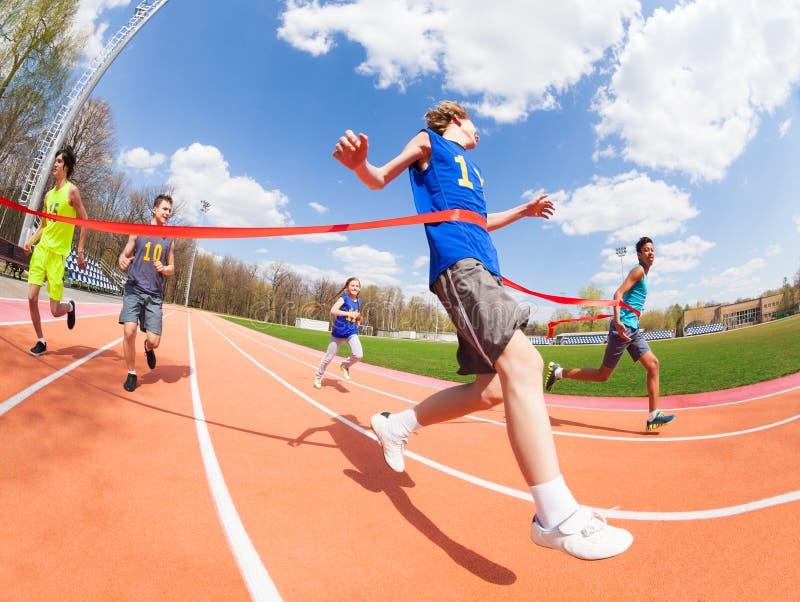 Le sprinter adolescent gagne en croisant la ligne d'arrivée photo libre de droits