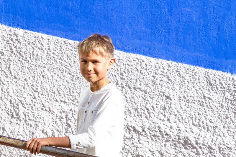 Le stående benägenhet för pojke mot trapparäcket utomhus arkivfoto