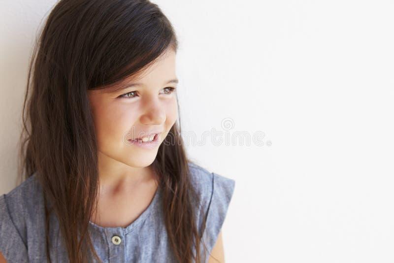 Le stående det fria för ung flicka mot den vita väggen royaltyfria bilder
