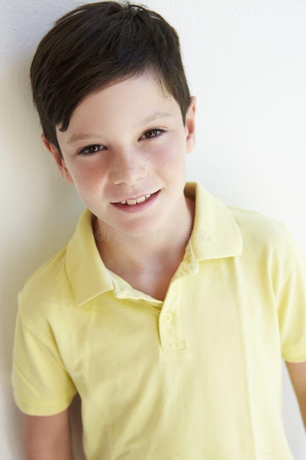 Le stående det fria för ung pojke mot den vita väggen royaltyfri foto
