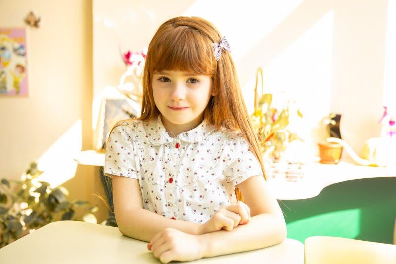 Le ståenden av rödhårig manflickasammanträde på ett skrivbord royaltyfri foto