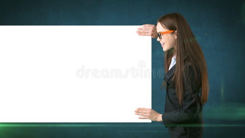Le ståenden för affärskvinnan med det isolerade tomma vita brädet på grå färger Kvinnlig modell med långt hår i exponeringsglas royaltyfri foto