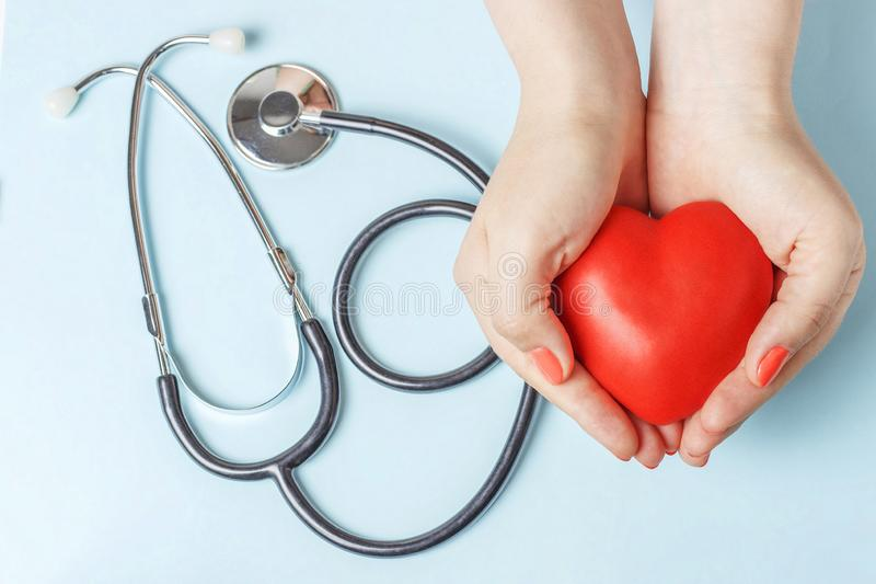 Le stéthoscope et le coeur rouge dans des mains femelles se ferment sur le fond bleu images libres de droits