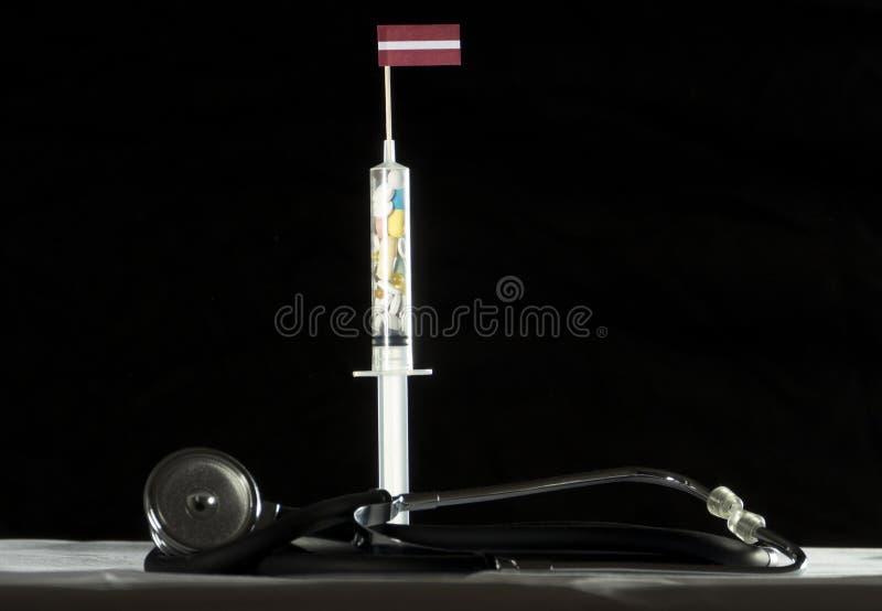 Le stéthoscope et la seringue ont rempli de drogues injectant le drapeau letton sur un fond noir photo libre de droits