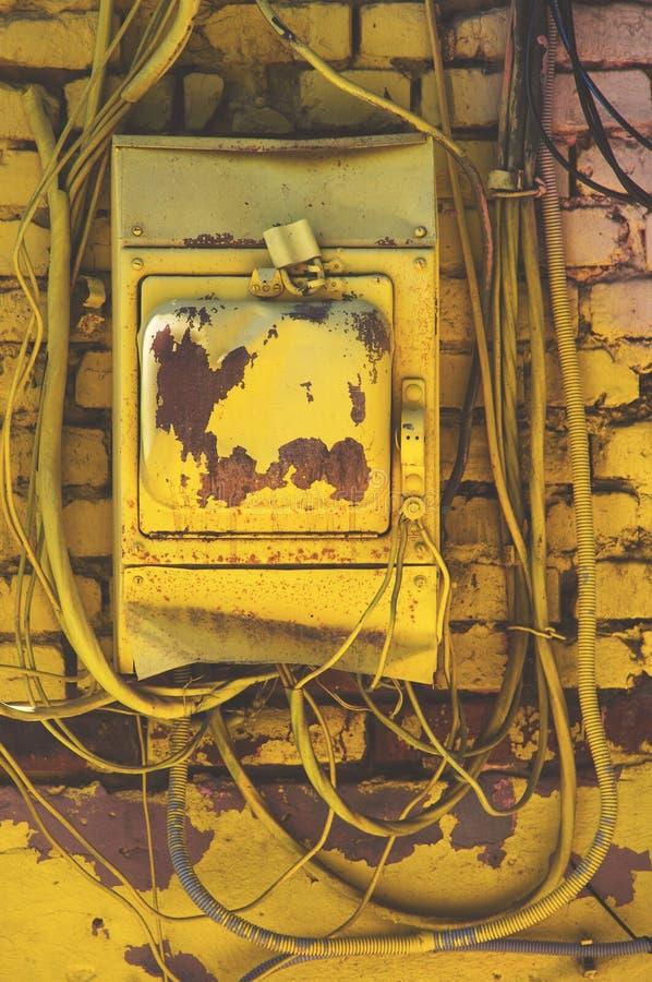 Le standard électrique a peint le jaune avec les fils chaotiquement saillants dangereux dans différentes directions sous la tensi photographie stock libre de droits