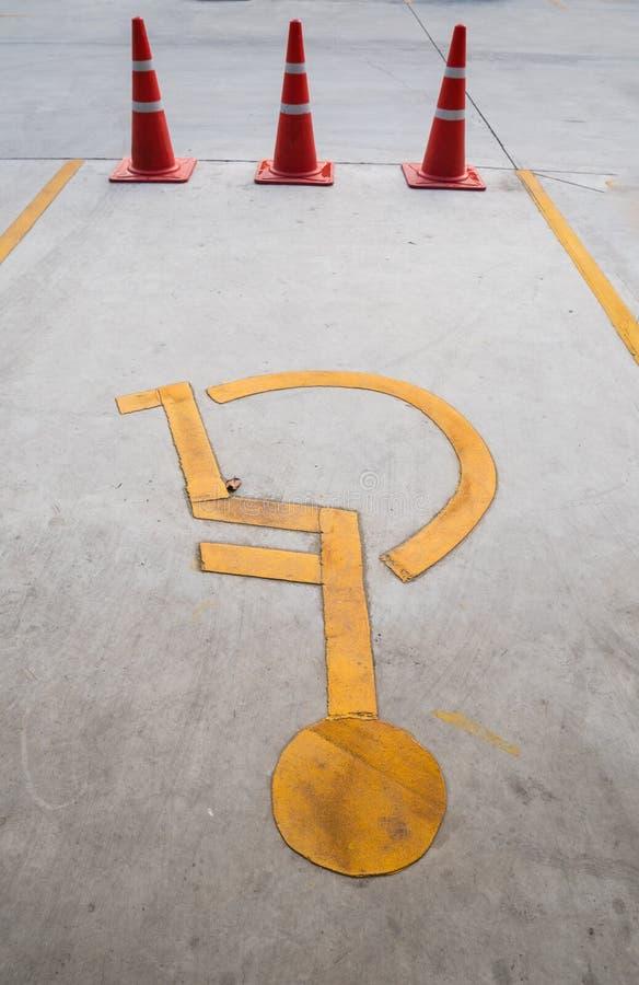Le stationnement handicapé ou les handicapés se connectent la route avec le cône du trafic image libre de droits