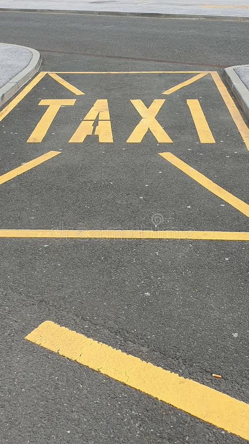 Le stationnement jaune de taxi se connectent une rue image libre de droits