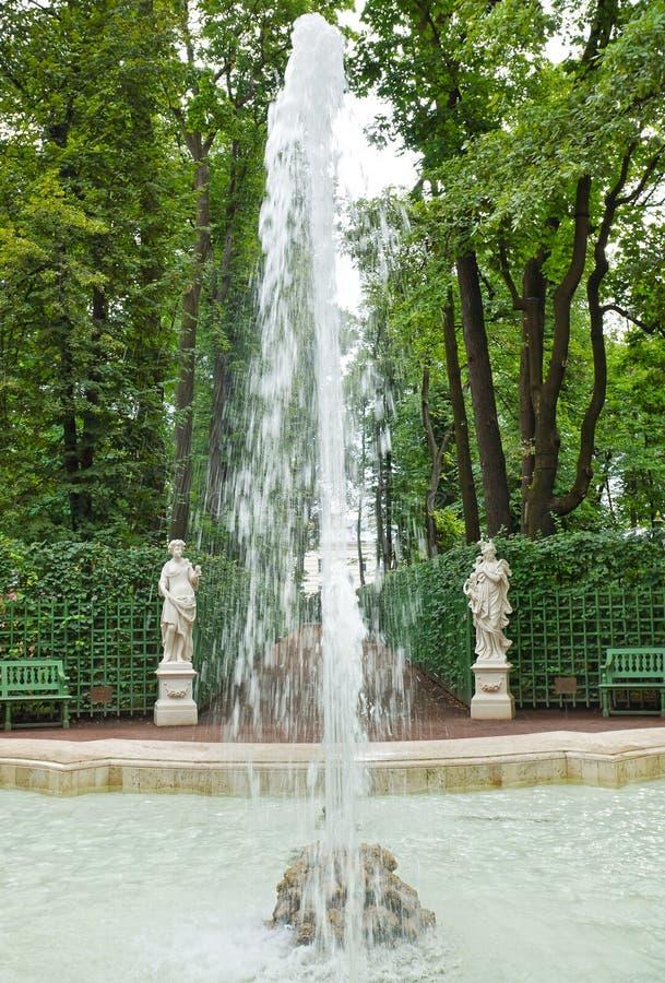 Le statue dell'oggetto d'antiquariato e della fontana nei giardini dell'estate parcheggiano fotografia stock libera da diritti